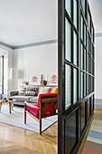 Black lattice and glass partition separating living room