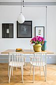 White spoke-back chairs around table with vase of pink anemones