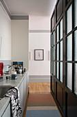 Schmale Küche mit schwarzer Trennwand mit Sprossenfenstern
