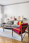 Colourful retro armchair and grey sofa in living room with high ceiling