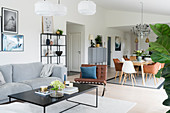 Sofa, coffee table, dining table and classic dining chairs in bright, open-plan interior