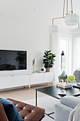 Flatscreen TV above low sideboard in white-and-grey living room