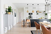 Open-plan kitchen and dining table with classic chairs in bright interior