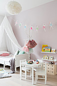 White canopy bed and garland of ballerinas in girl's bedroom with pink walls