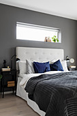 Double bed with button-tufted headboard in bedroom with dark grey walls
