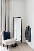 White easy chair, full-length mirror and clothes hook in corner