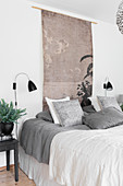 Oriental wall hanging and wall-mounted lamps above bed