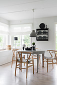 Designer chairs with fur seat cushions around traditional table in front of windows