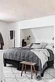 Bed in niche with sloping ceiling in bedroom in shades of grey