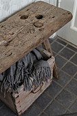 Blanket in wooden crate below old wooden stool