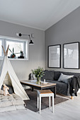 Grey sofa, coffee table, floor cushions and children's wigwam in corner of room