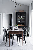 Black display cabinet, wooden dining table and bistro chairs in interior with grey walls