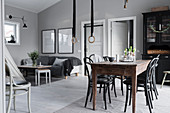 Lounge area, black display cabinet and dining table in grey interior