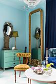 Goldrahmenspiegel neben türkiser Vintage-Kommode in Zimmer einer Altbauwohnung