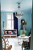 Antike Sitzbank neben Vintage-Kommode in Wohnraum mit blauen Wänden und Kronleuchter