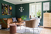 Armchair and leather sofa around coffee table and modern artwork on green living room wall