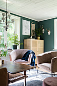 Armchair and half-height cabinet in living room with green walls