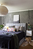 Collection of scatter cushions on double bed and lamp with fluffy lampshade in bedroom with grey walls