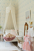 Canopied bed and pastel wallpaper in girl's bedroom