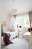 Canopied bed, large Miffy lamp and pastel wallpaper in girl's bedroom