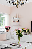 White furniture and fresh flowers in living room with tranquil pink walls