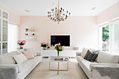 Sofa set, coffee table and TV stand in living room with tranquil pink walls