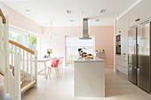 Offene Küche mit Kücheninsel und Essbereich vor Terrassentür