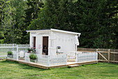 White playhouse with fence on platform in garden