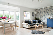 Dining table and sofa in bright, Scandinavian-style interior
