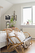 Rattan bench with cushions at foot of bed in bedroom with black-and-white photos on wall