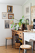 Retro radio and houseplant on two desks below gallery of pictures on wall