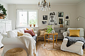 White, loose-covered sofa set and round table in country-house living room