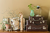 Various ornaments next to stacked vintage cases on top of chest of drawers