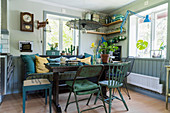 Dining table, wooden bench and various vintage chairs and stools in corner