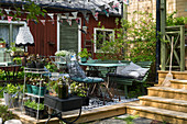 Wooden terrace decorated with potted plants and vintage-style garden furniture