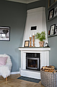 White corner fireplace in interior with grey walls
