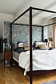 Four-poster bed with dark wooden frame against partition wall