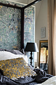Decorative, sequinned scatter cushion on four-poster bed against partition wall