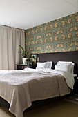 Double bed against wall with William Morris wallpaper