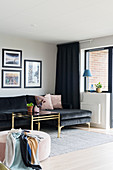 Black, velvet chaise sofa, brass coffee table and pink pouffe in living room