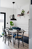 Table with bistro chairs and blue trunk bench in kitchen