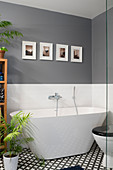 Modern free-standing bathtub in bathroom with grey walls and black-and-white tiled floor