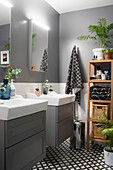Twin washstands and accessories on wooden shelves in grey bathroom