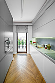Narrow, grey, modern kitchen with balcony door and parquet flooring