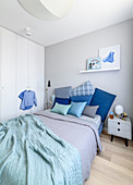 Cushions in shades of blue on double bed, bedside table and fitted wardrobes in bedroom