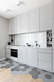 Pale grey kitchen cabinets in open-plan interior with two different floor coverings