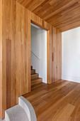Mit Holz verkleidete Wände und Decken im Flur mit Treppe