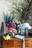Olive branches and various flowers in glass vases