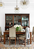 Upholstered chairs with high backs around dining table and antique china cabinet