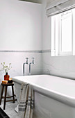 White bathtub under window in white bathroom